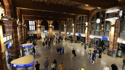 AMSTERDAM, NETHERLANDS - OCTOBER 20, 2018: Timelapse of a busy afternoon with many people crossing the main terminal of Amsterdam Central Station in the Dutch capital of the Netherlands