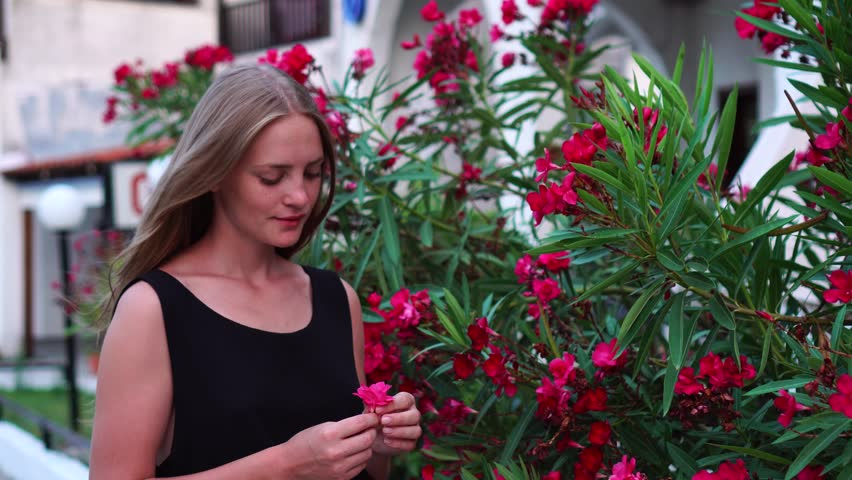 Beautiful tender dreamy young blonde girl observing wild nature sniffing wonderful tropical flowers on pink bush plant | Shutterstock HD Video #1018159828