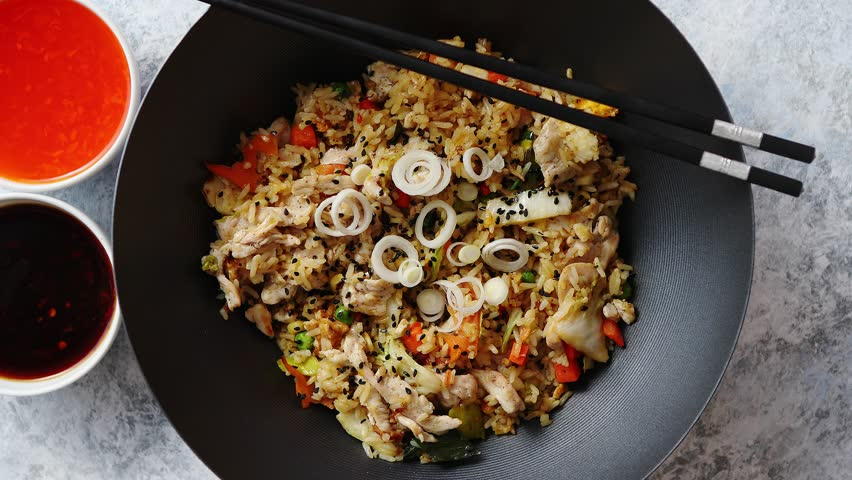 Delicious fried rice with chicken. Prepared and served in a wok with soy and sweet sour souces on side. Placed on stone background. Top view. | Shutterstock HD Video #1018207948