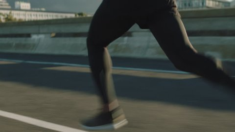 close up athlete legs running on road fit runner jogging sprinting endurance exercise in urban city morning at sunrise