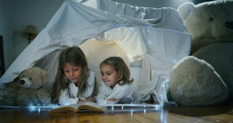 Two little girls sisters (kids) read stories in the dark under the blanket illuminating with a torch. Concept: Love, Family, Dreams