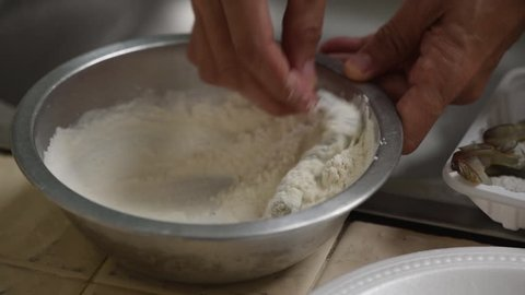 Mixing prawns with tempura flour for cooking