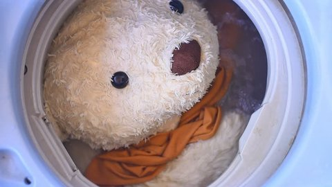Big teddy bears are being washed in the washing machine.