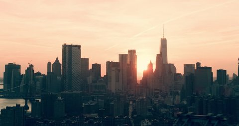 Aerial pan of downtown Manhattan and East River and Queensboro Bridge, New York City, bright sunset light. Wide shot. 4k shot with a RED camera.