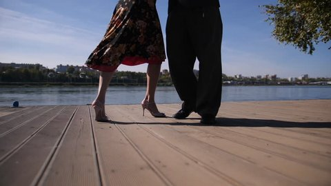 Tango dancers feet slow motion, beautiful woman and man dance on the coast river and floor, autumn sunny day