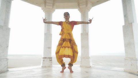 A wide shot of a Indian classical dancer dancing elegantly in white marble temple located on a hilltop. A moving shot of an attractive woman or lady making hand gestures in yellow traditional sari
