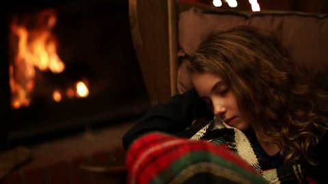 young girl is sleeping in a rocking chair by a warm fireplace
