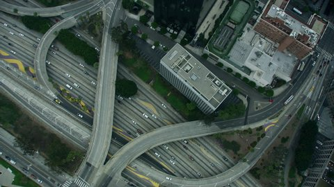 Aerial overhead rooftop view of heliport downtown Freeway intersection commuter traffic city skyscrapers banking business district road transport vehicles RED WEAPON