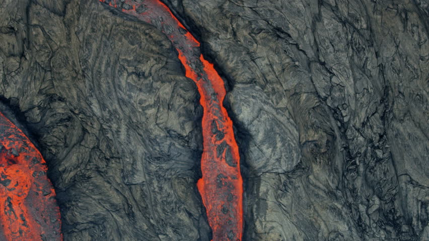 Aerial view of textured lava rock solidifying and cooling red hot lava rivers of liquid volcanic material pouring from the earths crust RED WEAPON | Shutterstock HD Video #1018444678