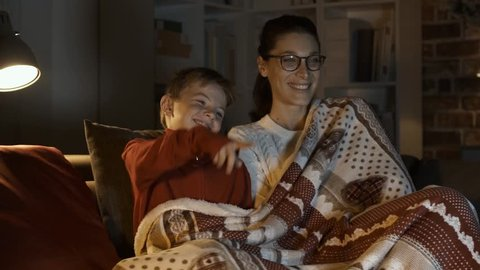 Happy mother and boy watching movies together on Christmas eve, they are sitting on the sofa and covering with a soft blanket