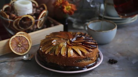 Plum cake decorated with sliced plum among the autumn decor. Cinemagraph.  Tea pours into the cup