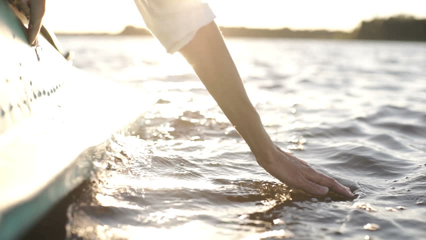 At sunset, close-up the hand of a girl moving through the water | Shutterstock HD Video #1018487548