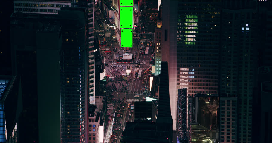 Aerial view of vibrant Times Square streets and buildings, New York City, bright night lighting. Wide shot on 4k RED camera with Green Screens.