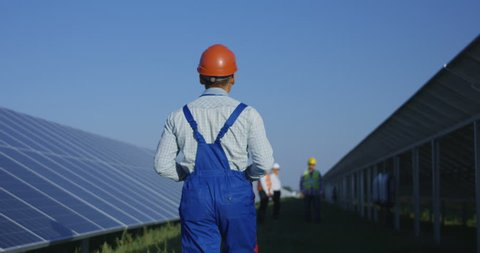 Medium shot from behind of an electrical technician walking with a tablet inbetween long rows of photovoltaic solar panels