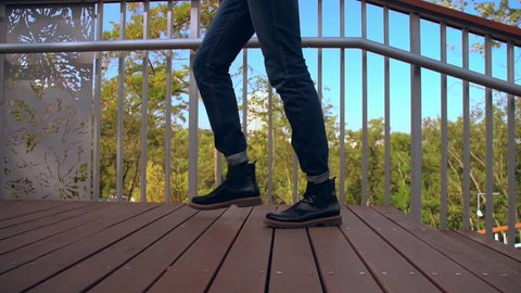 side view man climbs the stairs slow motion. close up details male legs wearing jeans and trendy shoes outdoors