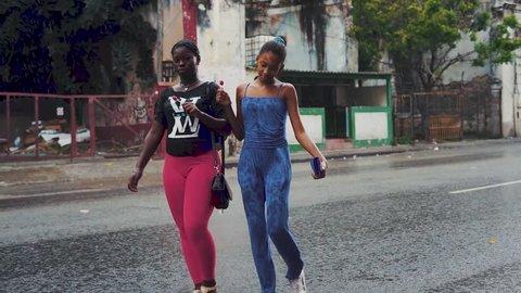 Havana, Cuba - 08 18 2018: young women cross the street in havana in the rain as vintage cars drive past