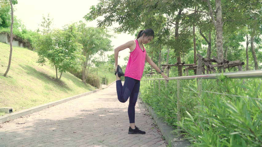 Healthy beautiful young Asian Athlete women in sports clothing legs warming and stretching her arms to ready for running on street in urban city park. Lifestyle active women exercise in city concept. #1018611058