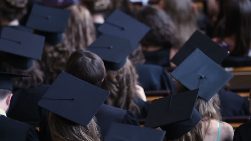 Excited graduates in mortarboards listening and applauding to motivating speech   Shutterstock HD Video #1018619668