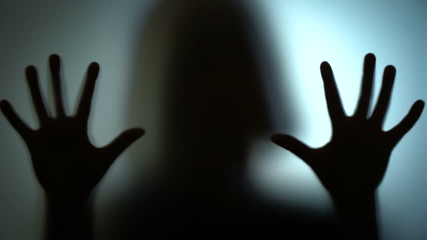 Silhouette of a deranged woman hammering on a glass, insane, lonely person. Blood-chilling horror thriller shot | Shutterstock HD Video #1018622338