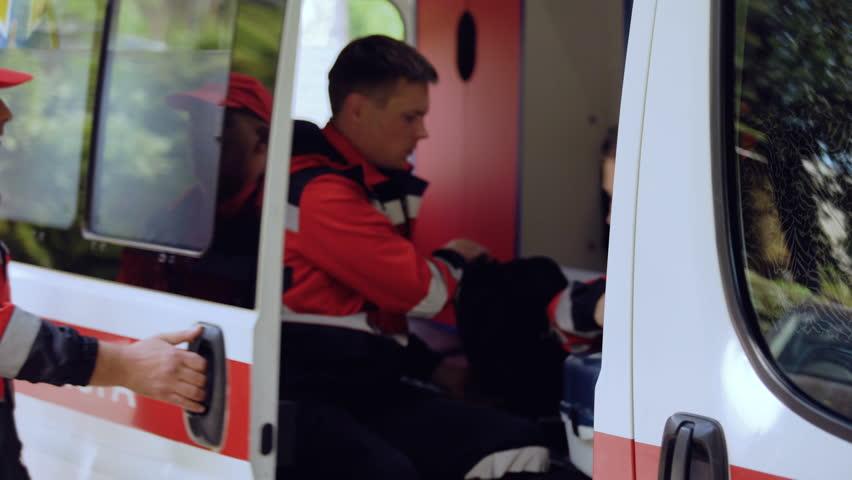 Ambulance crew leaving transport, paramedics walking to patient, urgent help