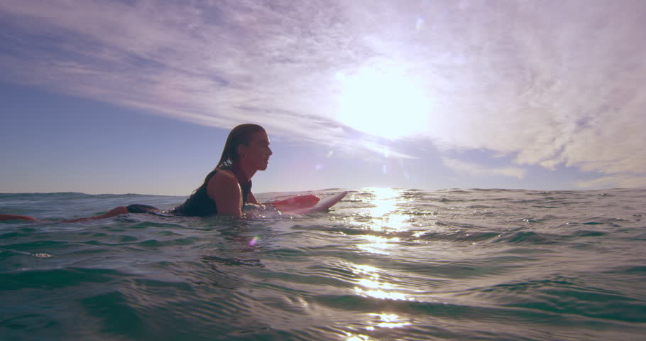 Athletic female surfer calmly swimming over an ocean wave on surfboard in Australian beach with bright day lighting. Wide shot on 4k RED camera. | Shutterstock HD Video #1018684018