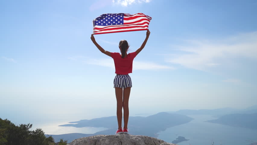 Child girl is waving American USA flag on top of mountain at sky background. Footage in slow motion #1018698118