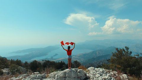 Aerial view: Child with Canadian flag on top of mountain, girl waving Canada symbol