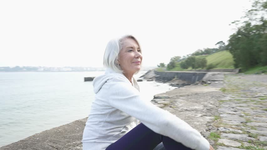Beautiful elderly woman sitting by the ocean in sportswear                               #1018737988