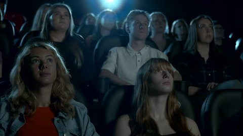 Teenage audience watching a movie at the cinema