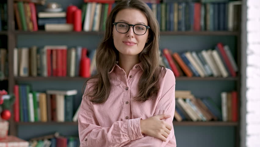 Close up portrait of young pretty librarian woman smiling happy looking at camera in library bookshelf background knowledge learning | Shutterstock HD Video #1018767388