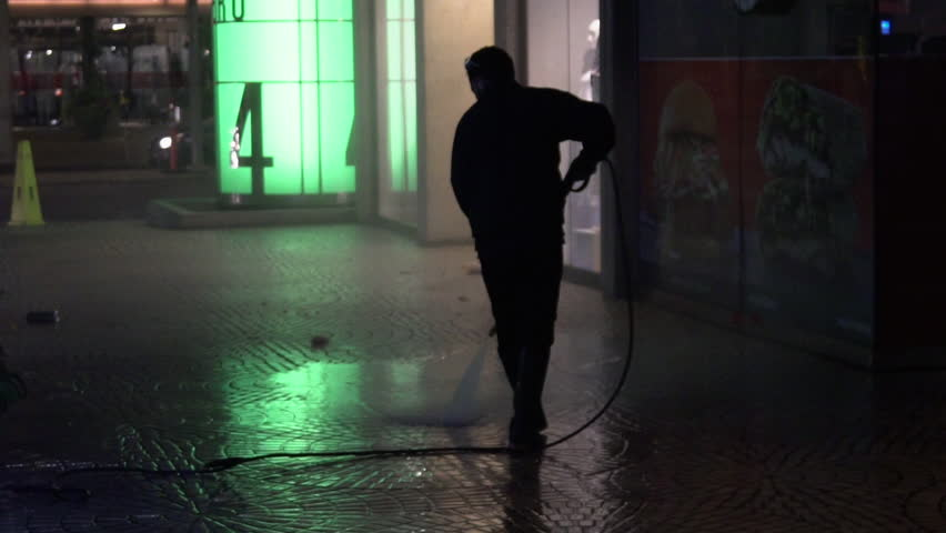 San Francisco, California / USA - August 9, 2018: Silhouetted man power washes the sidewalk at night in San Francisco   Shutterstock HD Video #1018791718