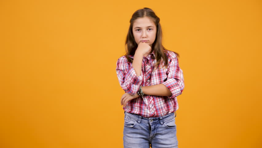 Young girl making silly faces in front of the camera on yellow orange background.  | Shutterstock HD Video #1018794298