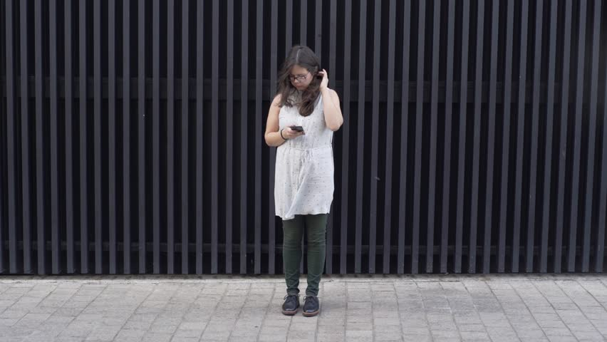Young girl standing in front of abstract wall.   Shutterstock HD Video #1018820098