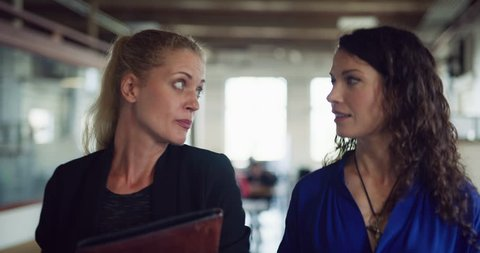 Two happy business women walk and talk down hallway in hipster industrial office during the daytime. Wide to medium shot on 4K RED on a gimbal.