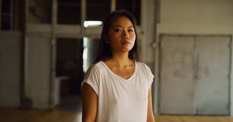Beautiful asian dancer pirouettes in industrial wood and brick windowed loft during daytime. Wide to long shot on 4K RED camera.