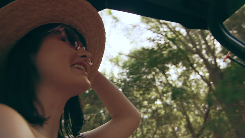 Beautiful woman wearing a hat and sunglasses driving an ATV through a forest in Australia, shaded natural lighting. Close up shot on 4k RED camera.