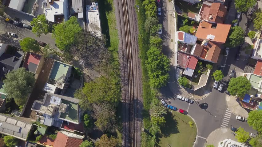 Aerial Drone Scene of Buenos Aires City, Argentina. Top View, Camera Moves Backwards Over Rooftops to Reveal Railroad Tracks. | Shutterstock HD Video #1018846108
