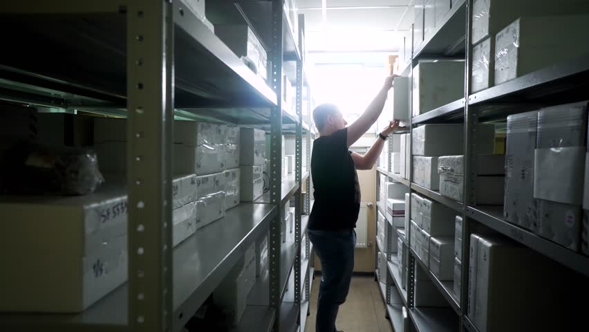 Warehouse worker puts or pulls a box from the rack in a small warehouse | Shutterstock HD Video #1018873108