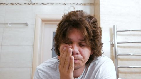 Sleepy shaggy young man cleans his teeth and looks at the mirror in bathroom in the morning.