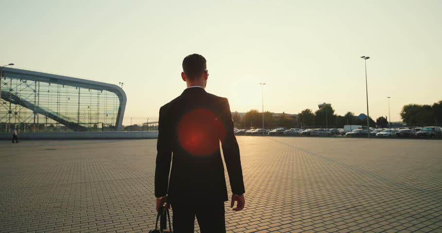 Back view on the Caucasian businessman with a bag in hand walking in a sunset sunligh at the big modern building background, two bears growth dolls following him and hugging. Outside. #1018904398