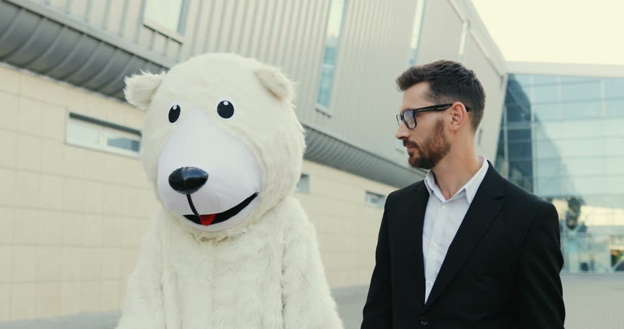 Portrait shot of the Caucasian man in the glasses and business style stopping at the street at the big urban buikding and hugging with a funny white bear growth doll. Outdoor.
