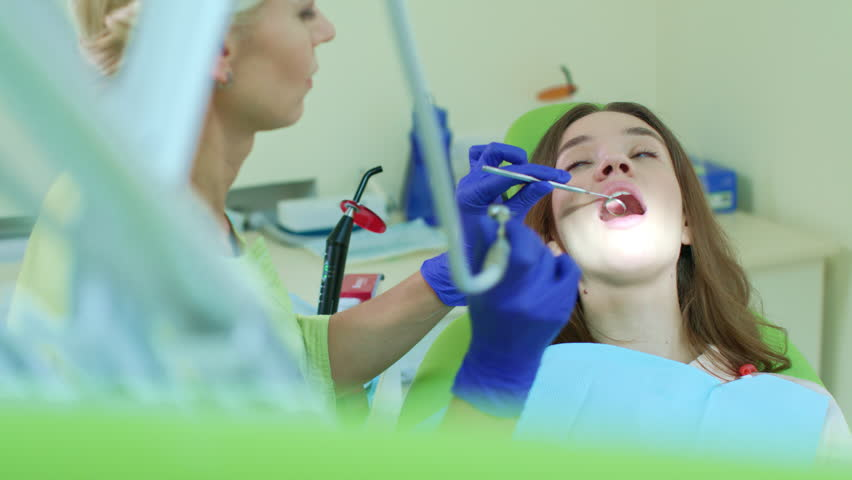 Stomatologist using high speed dental drill. Toothache treatment with dental instruments in dentist office. Dentist drilling patient sick tooth | Shutterstock HD Video #1018955998