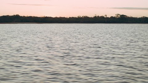 Waves on lake with shore in the distance and beautiful sunset in Australia. Medium close on 4k RED camera.