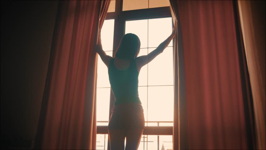 Lovely girl is awake and standing before window. Beautiful woman opening curtains and looking through the window. #1018970338