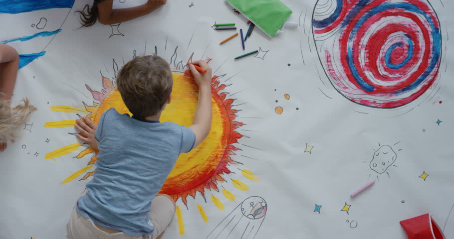 Young diverse children paint colorful space pictures together on paper using paint brushes happy kids enjoying fun creativity painting science fiction space drawing pictures top view