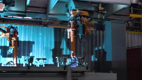Close-up of welding of metal parts by welding machine at factory. Scene. Large industrial robots-welders of metal auto parts