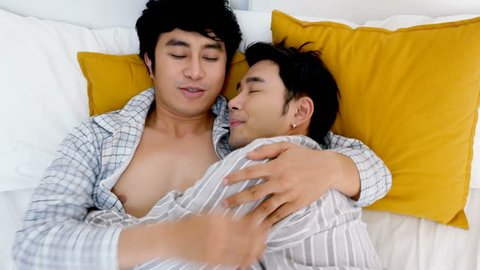 Gay couple with resting together in bedroom. People with gay, homosexual, relationship concept.