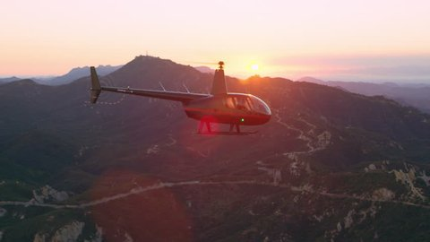 Aerial view of helicopter flying over mountain range during purple and pink sunset in Los Angeles, California. Wide long shot on 4K RED camera.