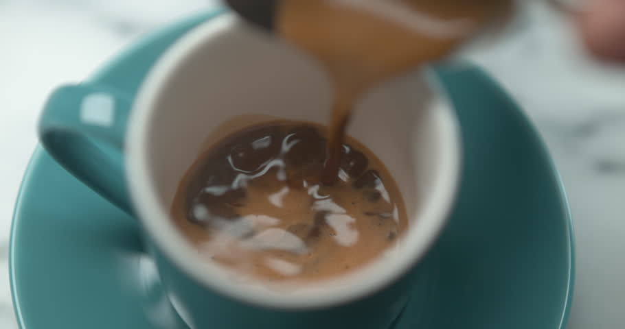 Barista pouring espresso in blue small cup in ultra slow motion closeup with 4k Phantom Flex camera.