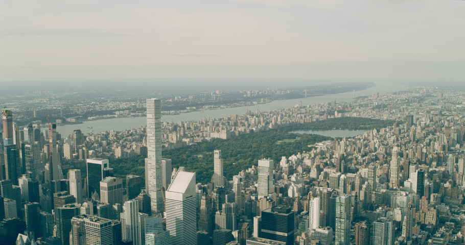 Aerial view of Central Park and Manhattan skyine in New York during the day under blue skies. Wide shot on 4K RED camera.